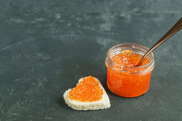 Red caviar sanwiched on gray background,  sea food. healthy eating and diet. copy space for text