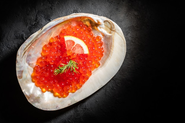 Red caviar in the sea shell on black table.