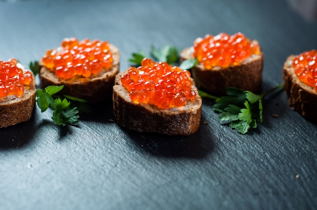 Red caviar on slate background