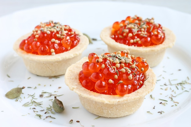 Red caviar in tartlets on white plate