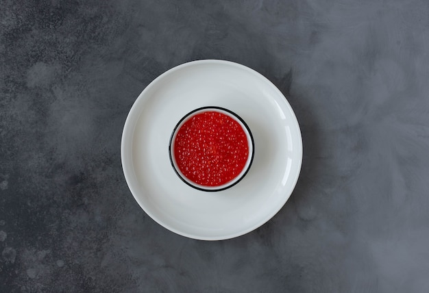 Red caviar in a white plate on a dark background. top view. copy space