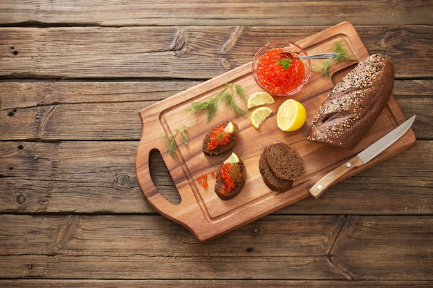 Red caviar with black bread, dill and lemon on  wooden board