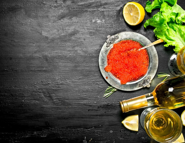 Red caviar with a bottle of white wine. on a black chalkboard.