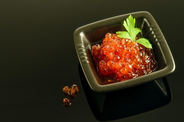 Red caviar with green parsley in the littles black bowl on the black reflective background. healthy delicious food.
