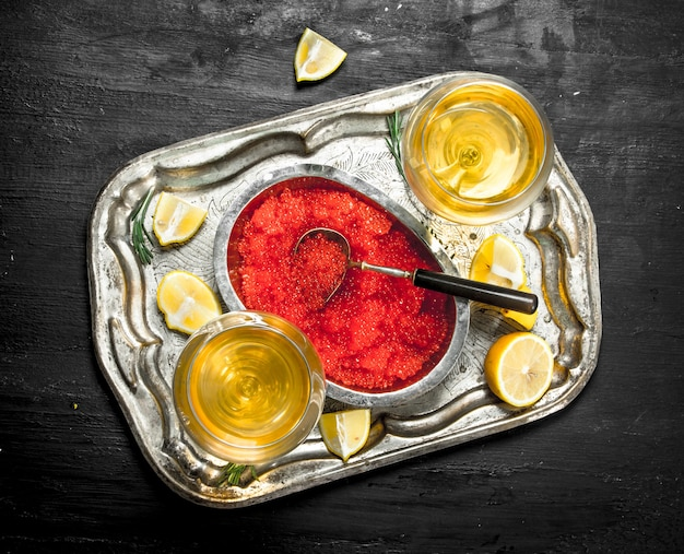 Red caviar with white wine on the old tray. on a black chalkboard.