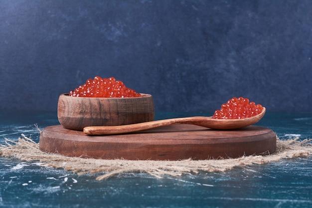Caviale rosso su tavola di legno.