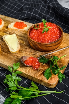 Red caviar in wooden bowl and sandwiches on cutting board. top view