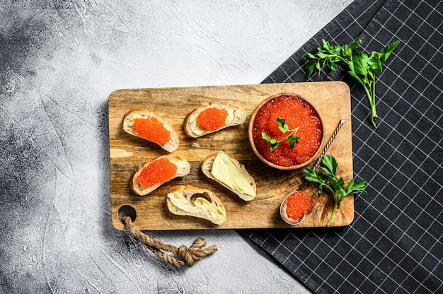 Red caviar in wooden bowl and sandwiches on cutting board. top view.
