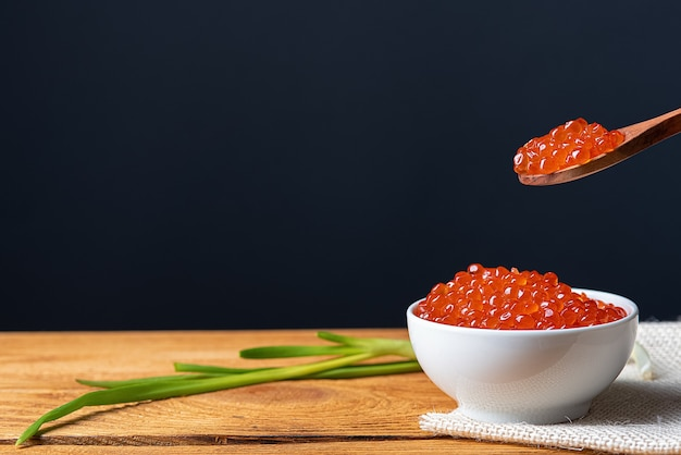 Red caviar in a wooden cup on a wooden background with a spoon. place for advertisement, logo, label, mockup, mock-up.