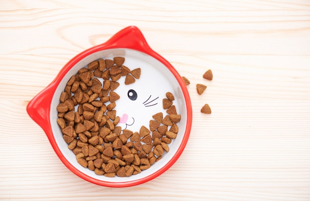 Red ceramic bowl fith dry pet nutrition food brown food for cat