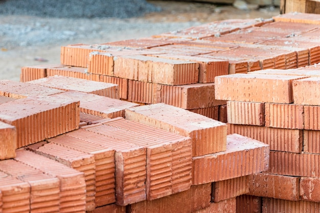 Red ceramic bricks stacked on a construction site. construction materials. red brick for building a house.