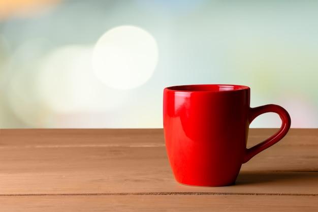 Красная керамическая чашка на деревянных фоне