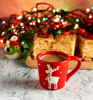 Red ceramic cup with black coffee near green branches of spruce and christmas toys