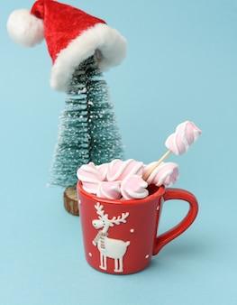 クリスマスツリーの後ろに、ココアとマシュマロが入った赤いセラミックカップ