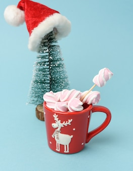 Red ceramic cup with cocoa and marshmallows, behind a christmas tree