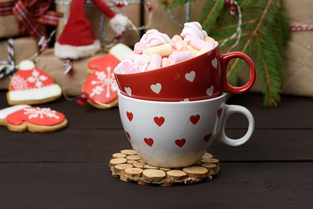 Red ceramic cup with cocoa and marshmallows, behind a gift box and a christmas garland, close up