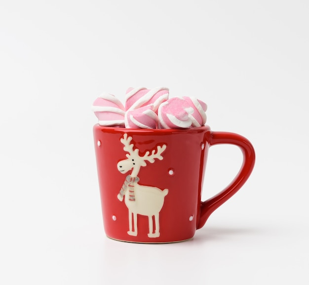 Red ceramic cup with cocoa and marshmallows on a white background, close up