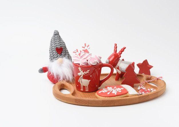 Red ceramic cup with cocoa and marshmallows, white background