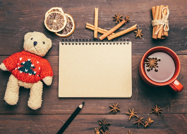 Red ceramic cup with cocoa, notepad with blank sheets and brown teddy bear toy on a wooden table, top view