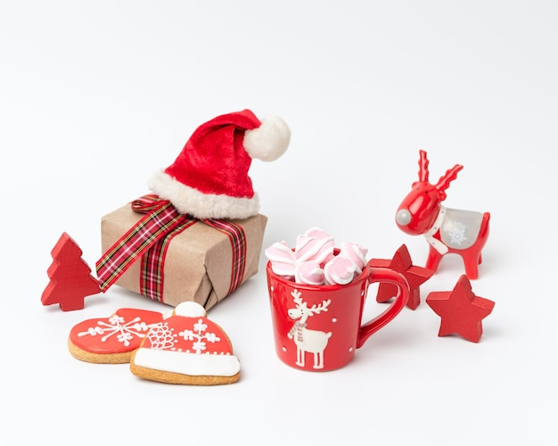 Red ceramic cup with drink and marshmallows, near baked christmas gingerbread, white background