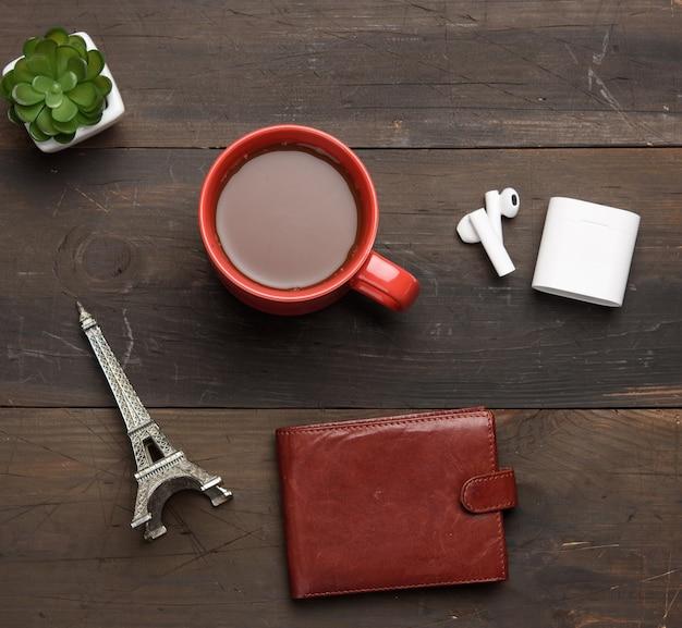 ブラックコーヒー、革の茶色の財布、木製の茶色のテーブルにワイヤレスヘッドフォン、上面図と赤いセラミックマグカップ