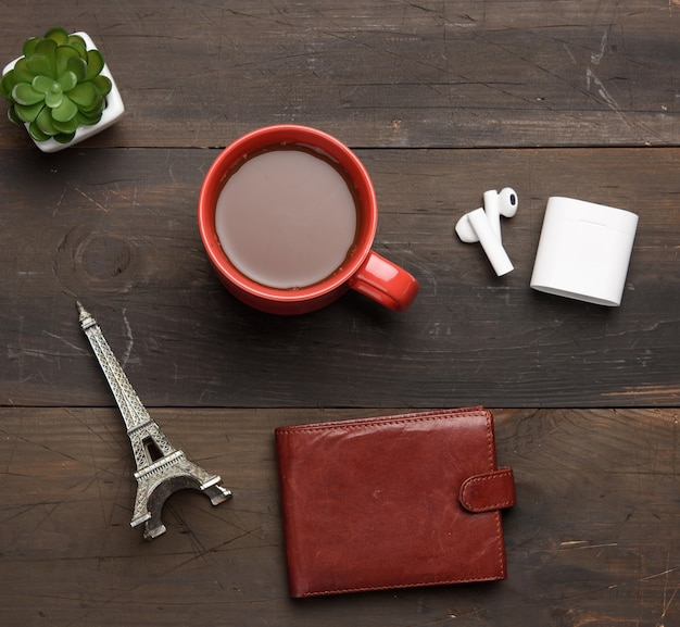 Red ceramic mug with black coffee, leather brown wallet and wireless headphones on a wooden brown table, top view