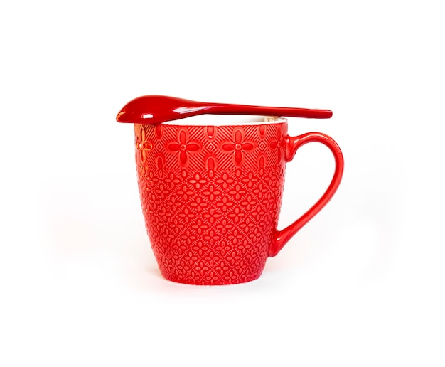 それの上に横たわる赤いセラミックスプーンと赤いセラミックマグカップ