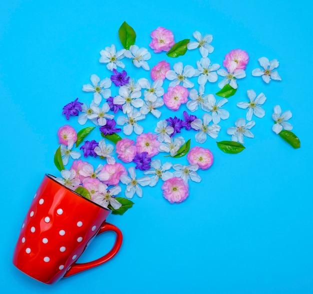 Of red ceramic mug with white polka dots randomly poured flower