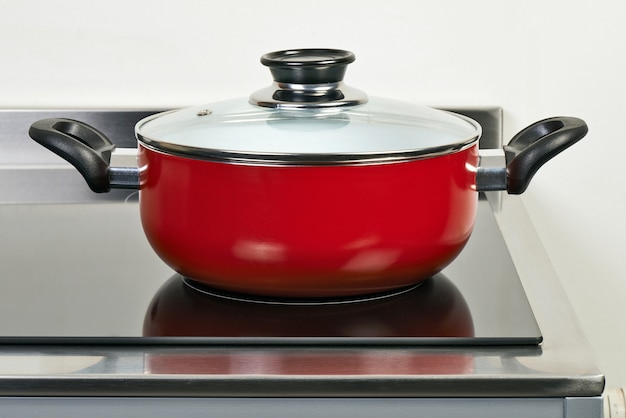 Red ceramic pan with cover on electric hob