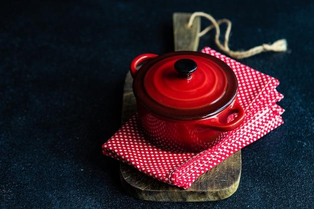 料理の概念としての暗いコンクリートのテーブルに赤いセラミックポット