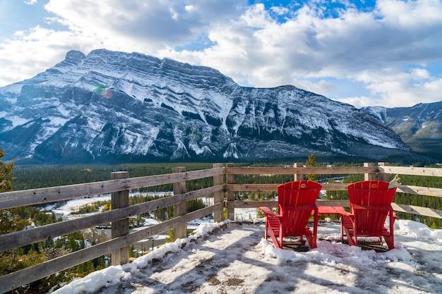 눈 덮인 겨울 화창한 날 밴프 국립 공원의 아름다운 풍경에 빨간 의자가 런들 산을 내려다보고 있습니다.
