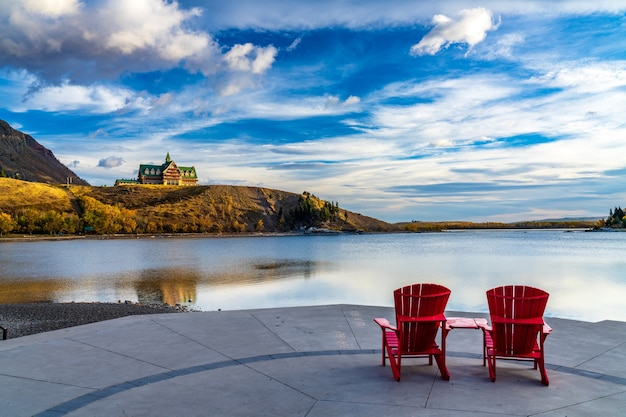 Красное кресло смотрит на озеро уотертон в марина пойнт в солнечное утро сезона осенней листвы. национальный парк уотертон-лейкс, альберта, канада.