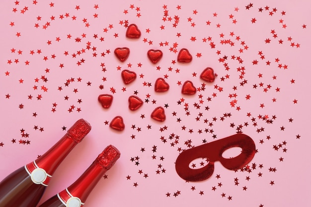Red champagne bottles with red chocolate hearts and carnival mask on pink. copy space