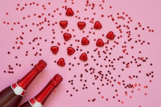 ピンクの背景に赤いハートの赤いシャンパンボトル。コピースペース、上面図