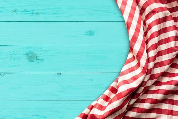 Красная клетчатая ткань на синем фоне деревянного стола