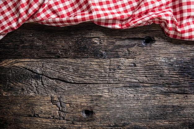 素朴な木製のテーブルに赤い市松模様のキッチンテーブルクロス。