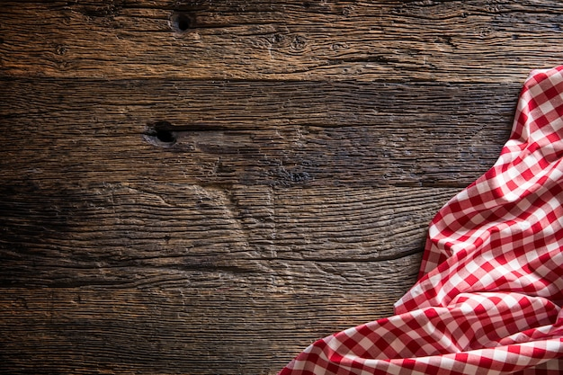 소박한 나무 테이블에 빨간색 체크 무늬 주방 식탁보입니다.