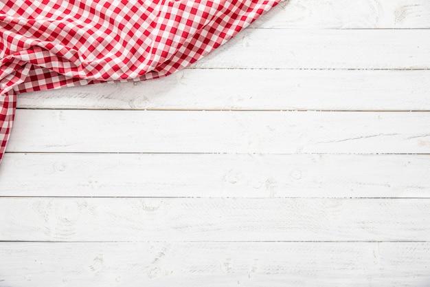 木製のテーブルに赤い市松模様のキッチンテーブルクロス。