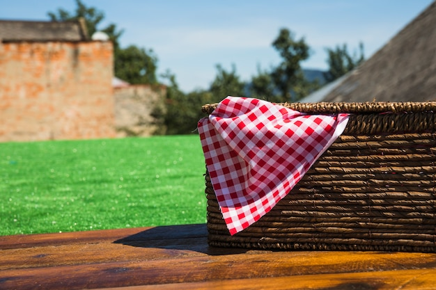 Red checkered napkin inside the picnic basket on wooden table at outdoors