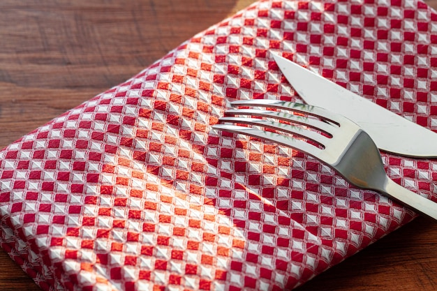 Red checkered napkin or tablecloth  on wooden table, copy space
