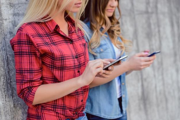 빨간색 체크 무늬 셔츠 중독 생활 방식 여가 휴식은 소셜 미디어 사람들이 야외에서 십대 아름다움 개념에 집착하는 그룹을 이완합니다. 고립 된 회색 배경 손에 전화를 들고 여자의 사진을 닫습니다
