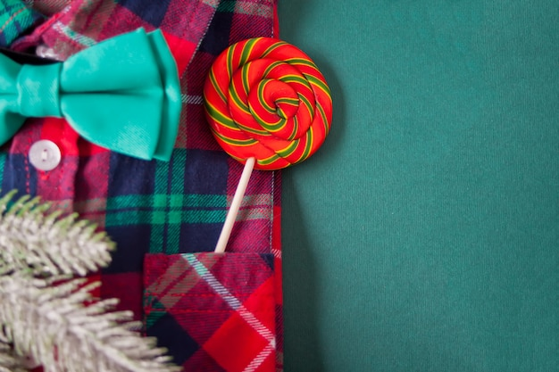 Red checkered shirt, tie butterfly, pine branch, lollipop in a pocket on the green background