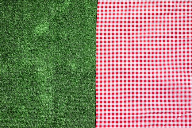 Red checkered table cloth and green turf background