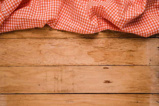 Red checkered table cloth at the top of old wooden worktop