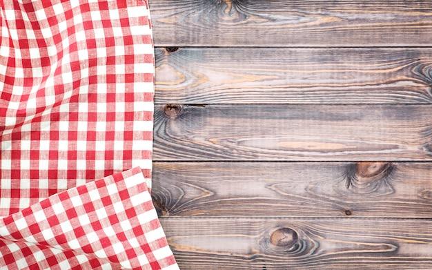 Красная клетчатая скатерть на светлом деревянном столе с, вид сверху с копией пространства