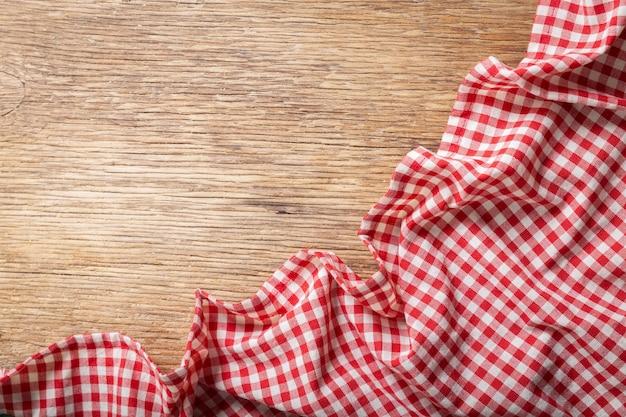 Красная клетчатая скатерть на деревянном столе, вид сверху