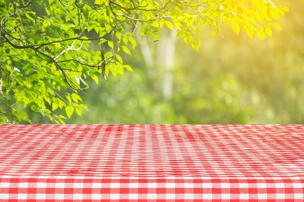 추상 녹색 bokeh 배경으로 빨간색 체크 무늬 식탁보 질감 상위 뷰