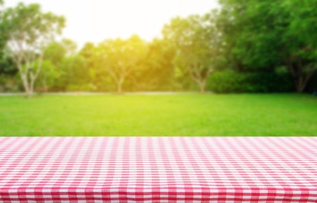 정원 배경에서 추상 녹색 보케가 있는 빨간색 체크 무늬 식탁보 질감 상위 뷰