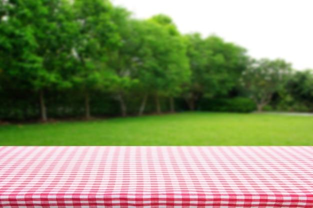 朝の庭から抽象的な緑のボケ味と赤い市松模様のテーブルクロスのテクスチャ上面図