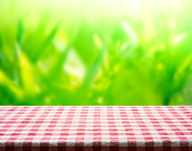 Red checkered tablecloth texture top view with abstract green bokeh from garden in morning background